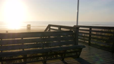 ławka : View of Bench by the beach during sunrise