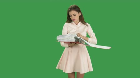 segregator : Office young woman with a full paper document binder against green screen. Searching through the sheets and not finding what she looking for. Perplexed and disappointment final against greenscreen