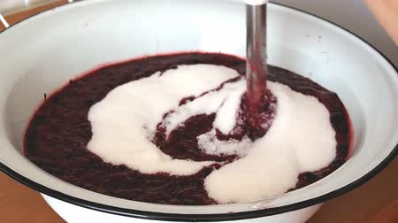 groselhas : Woman blending jam with blackcurrants and sugar in a large bowl