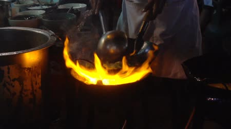 south asian food : Street-side wok fire in Chinatown Bangkok. Cook fired up hot oil with vegetables outside on the road at night in downtown Yaowarat road food street in Thailand. Stock Footage
