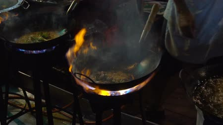 Street-side wok fire in Chinatown Bangkok. Cook fired up hot oil with vegetables outside on the road at night in downtown Yaowarat road food street in Thailand. Стоковые видеозаписи