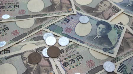 Close up of Japanese coin yen falling on banknotes 1000 and 10000 yen background. Super slow motion 120 fsp with sound. Стоковые видеозаписи