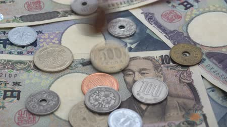 Close up of Japanese coin yen falling on banknotes 1000 and 10000 yen background with sound