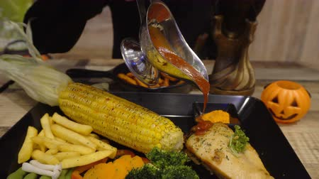 Chicken steak with corn and potatoes on a black plate and cola drinks, pumpkin at the Halloween party. Стоковые видеозаписи