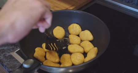 nugget : fried chicken nuggets meat are being cooked deep fried in a hot boiling oil pan