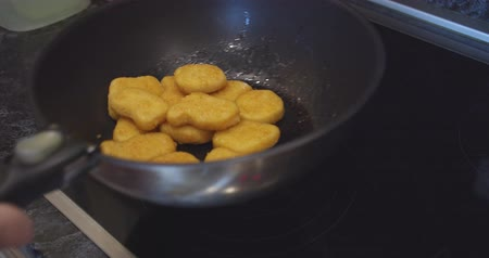 маслянистый : fried chicken nuggets meat are being cooked deep fried in a hot boiling oil pan