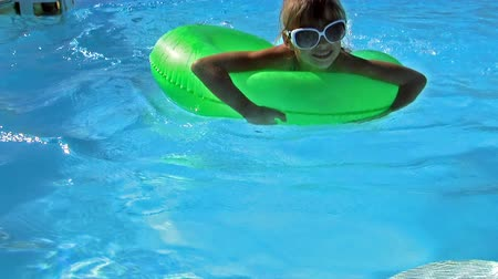 halkalar : Children sitting on inflatable ring in swimming pool. Stok Video