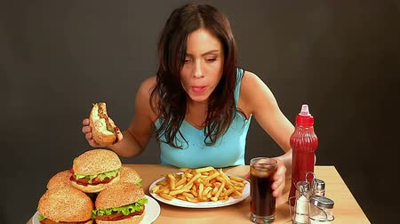 быстрый : Woman eating fast food.Slim girl absorbs  huge amount of food .Time lapse.