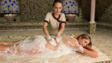 wanna : Girl enjoys of turetskim massage in hammam . Camera moves . Shooting with dolly crane system.