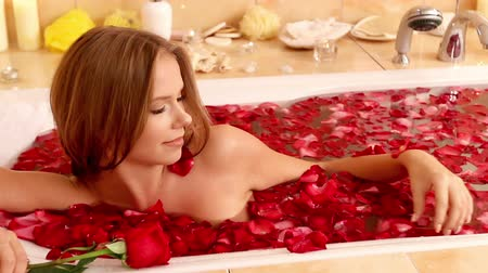 banyo : Girl takes bath with rose petals. Takes them in his hand and throws it in water again. Shooting with a tripod .