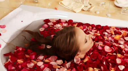 wanna : Girl takes bath with rose petals. Immersed in water and floats on back.  Camera moves . Used dolly system Wideo