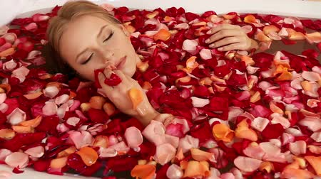 wanna : Girl takes bath with rose petals. Submerged entire water only person on the surface