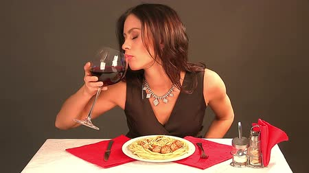 comer : Happy woman eating spaghetti with beef and drinking red wine in restaurant. Time lapse.