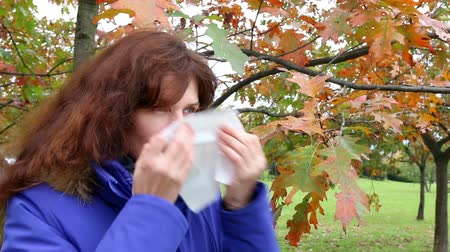nariz : Woman blowing his nose and vigorously goes on at autumn park. Outdoor. Vídeos