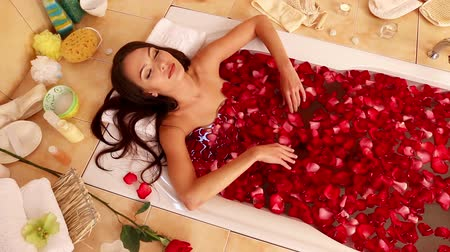 wanna : Very beautiful girl with long beautiful hairl takes a bath with rose petals. The camera moves from the face to the feet. In the background is burning candles and bath accessories. Used dolly crane system.