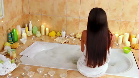 banyo : Brunette young woman going to take bath  in her bathroom. Girl sitting on edge of  tub and slowly takes off her towel.