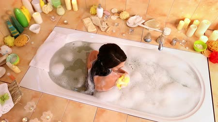 hot tub : Young woman taking foam bath and wash sholder by yellow  wisp of bast in her bathroom. Top view. Cran system.