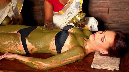 bahno : Two women Indian beautician applied therapeutic composition of natural ingredients to patients body. Used steadicam.