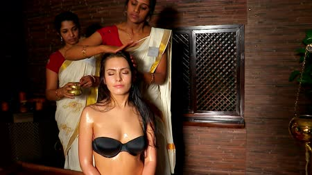 hint : Young woman having head ayurveda treatment. Two real Indian girl masseuse in  ayurvedic spa salon. Camera moving forward.