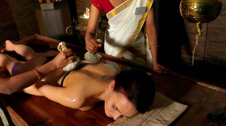 bitkisel ilaç : Woman having ayurvedic back massage with pouch of rice. One can see only dark hands with bracelets of Indian masseuses. Used steadicam.