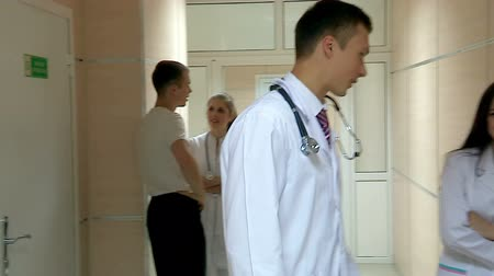 medicals : Young doctor are walking on the hallway of the hospital, with all the greeting and then comes into his office. Used steadicam.