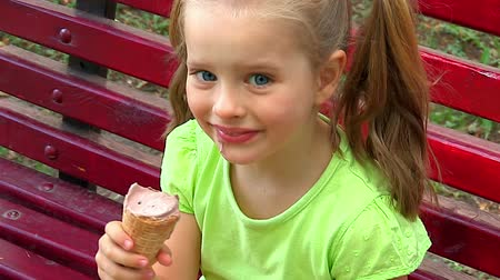 dondurma : Child eating ice-cream sitting on bench in park outdoor and show thumb up. Stok Video