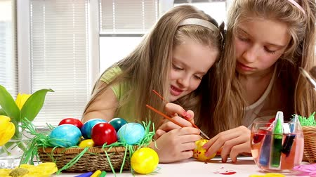 springtime : Children girl paint Easter eggs at home. Flowers in basket.