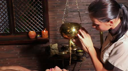 лечение : Young woman having Ayurveda spa treatment. Masseuse pouring oil on head of client. Стоковые видеозаписи