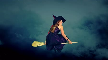 ведьма : Beautiful young witch flying on broom breaking through cloud mass. Halloween witch wearing witch hat. Стоковые видеозаписи