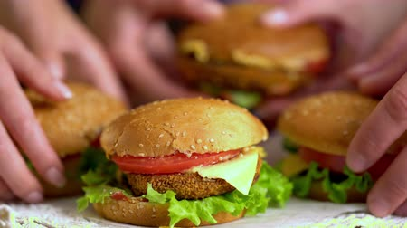 lacy : Hamburger fast food with ham on wooden board on lacy napkin. Group of hamburger in female hands on background.4k Stock Footage