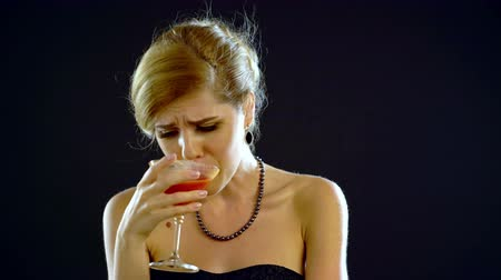 unrequited : Girl drinking martini and crying. Girl dressed in an evening dress. Black background. 4k.