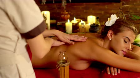 masaż : Young woman lying on wooden spa bed. Massage in spa salon with masseuse. Masseuse pouring oil in his hand and begins to massage. Girl on candles background in massage spa salon. 4k. Wideo