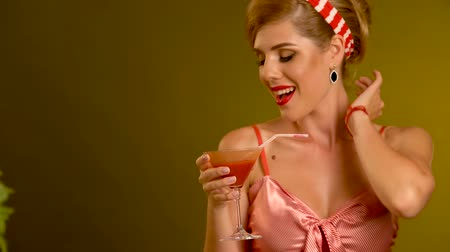pinup : Pin up girl drink bloody Mary cocktail and dancing . Pin-up retro female style. Girl pin-up style wearing red dress. Have a copy space.