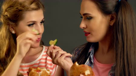 навынос : Burger women eating fast food with ham . Friends girls eating sandwich junk in party. Loving couple lesbians feed each other in cafe.