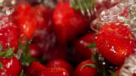 ambientalmente : Strawberry watering. Close up of crop of picked freshly red berry and green leaves in cold water with chaotic motion.