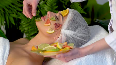 prosedür : Facial mask from fruits for woman. Skin care with fruit on face in spa salon. Beautician apply slices of avocado, grapefruit and kiwi girl in medical hat lying on bed for procedure near green plant.