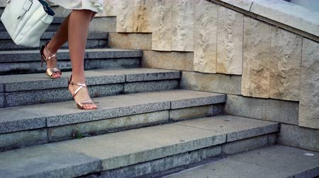 испуг : Girl runs on steps down on high heels stiletto in street city outdoor. Side low angle by legs and shoes summer sandals also border of white dress.