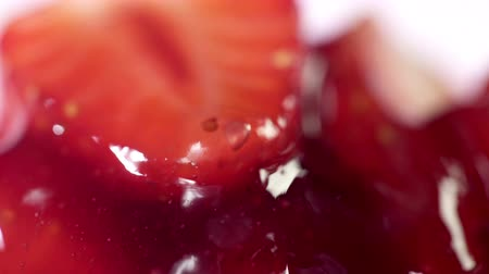 Macro strawberry jam dessert syrup pouring on moving sticky spoon. Cooking home canned confiture food.