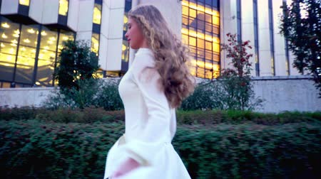 szandál : Girl with long blond hair runs on evening street outdoor. Young woman in white dress is in hurry to date in night city.