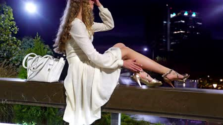 Girl sitting in street city with stainless steel street lamps. Young woman in white dress and summer shoes , near natural leather bag rest in solitude.