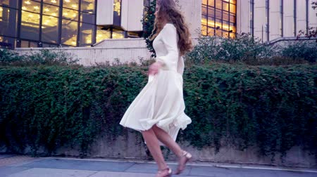 Girl runs on high heels stiletto in street city outdoor. Young woman in white dress and summer shoes swinging bag of natural leather hurries along sidewalk.