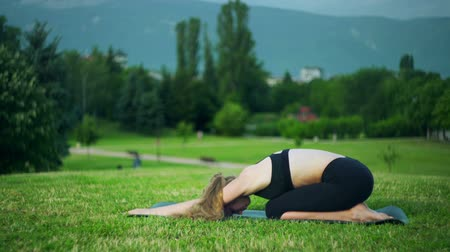Girl doing yoga basics in park outdoor. Morning sunlight on young woman sitting in child pose position sun yogalates summer on green grassand flying birds and city background.