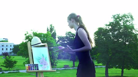 Girl draws on plein air. Young woman with easel and watercolor paints paints flowers on green grass in city park.