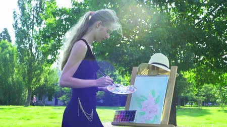 Girl draws on plein air in solitude. Young woman with easel and watercolor paints painting flowers on green grass under tree in city park.