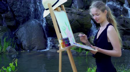 Girl draws on plein air. Young woman with easel and watercolor paints paints flowers on green grass in city park. Mountain waterfall and lake on background.