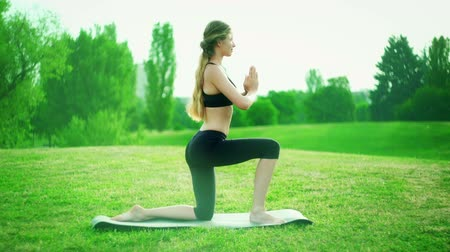 Girl doing yoga in mystical fog and rainbow light park outdoor. Morning sunlight through mist on young woman in sun salute kneeling pose yogalates . Wideo