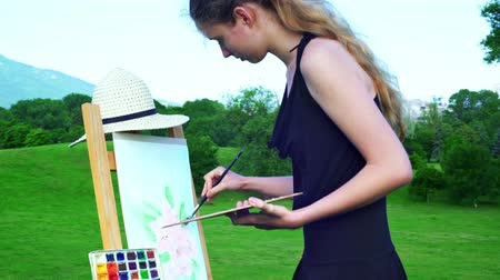 Girl draws on plein air in solitude. Young woman with easel and watercolor paints painting flowers on green grass next to trees in city park mountain background.
