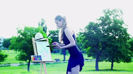 park paths : Girl draws on plein air with light wind. Young woman with easel and watercolor paints painting flowers on green grass and asphalt paths city park. Camera moves around artist wear black evening dress. Stock Footage