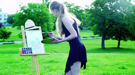 Girl draws on plein air. Young woman with easel and watercolor paints painting flowers on green grass and asphalt paths in city park. Camera moves around artist.