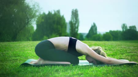 Girl doing entry level yoga in park outdoor. Morning sunlight on young woman sitting in child pose position sun yogalates summer on green grass.